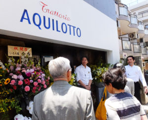 待ちにまった開店を前にあいさつをするシェフの工藤さん(右)、ソムリエの長谷川さん(中央)。多く著名人や地元企業からの花も鮮やかに、前店時代の常連客も駆け付けた中での2人の新たな船出となった