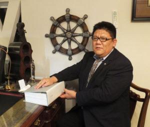 日吉本町東町会会館での無料相談会も満10周年。同相談会における多岐にわたる相談内容のファイルを手にする行政書士・海事代理士の加賀雅典さん