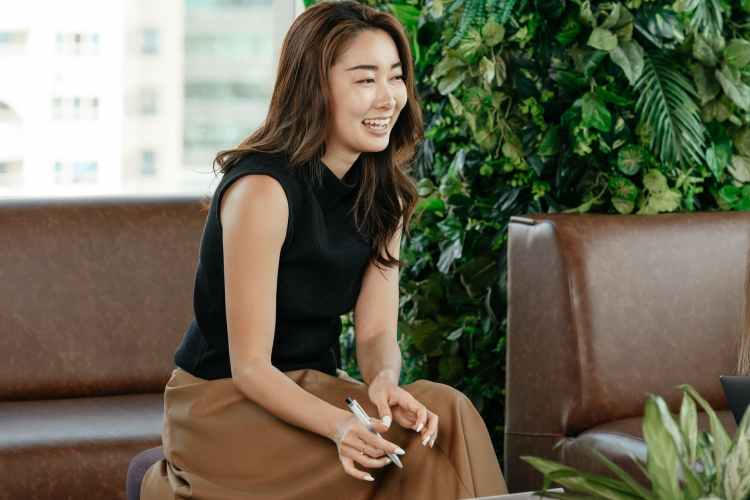 cheerful asian woman in elegant outfit on leather sofa