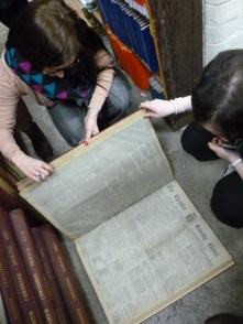 Rosie looking at a bound book of old newspapers, under the supervision of Emma