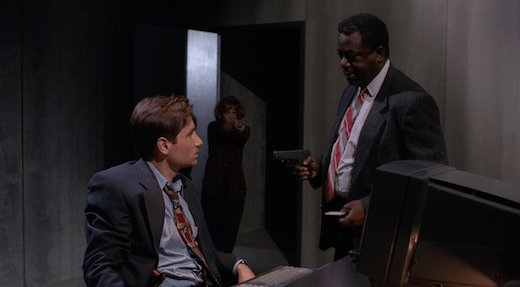 Mulder and Peterson argue, neither seeing that Scully has just walked in with her gun raised.