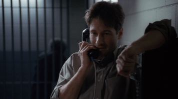Mulder speaks to Scully on the phone from jail.