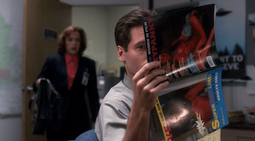 Mulder holds up a porn magazine vertically, presumably to look at the centerfold.