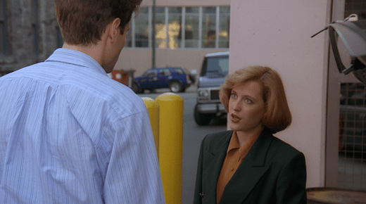 Scully is looking up at Mulder.