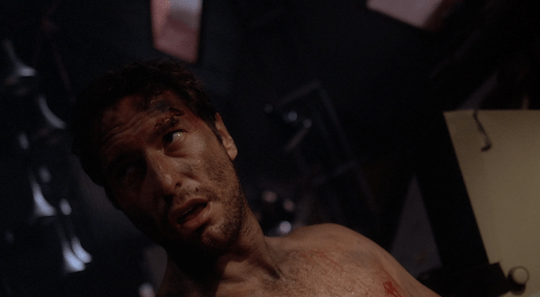 A shirtless, sweaty, visibly ill man leans back in a chair.