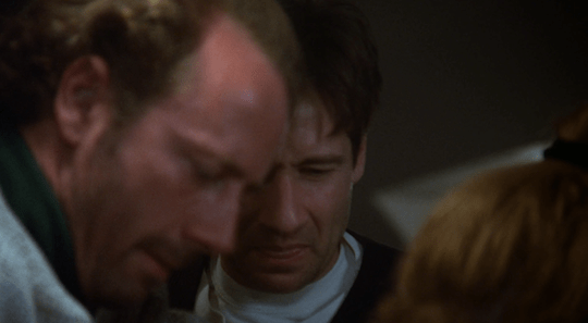 Mulder grimaces much like Scully at the grossness of Bear's infection.