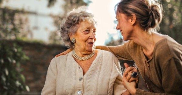 Joyful adult daughter greeting happy surprised senior mother in garden