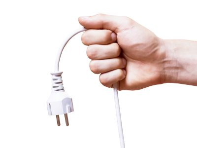 Image of hand holding an unplugged power cable.