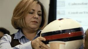Rep. Linda T. Sanchez inspects football helmet in a former hearing on Capitol Hill in Washington, DC.