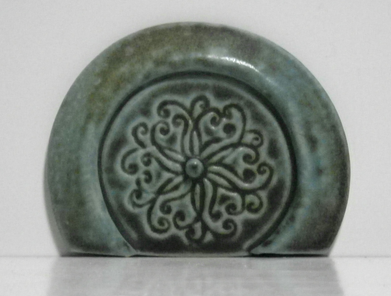 small green round hobbit style fairy door embossed with a swirl pattern