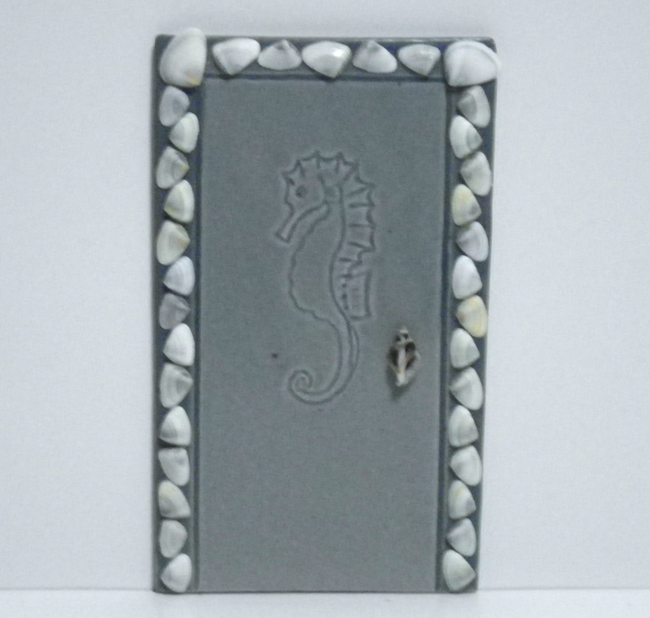 Tall, rectangular, blue-gray fairy door embossed with a seahorse, framed with seashells
