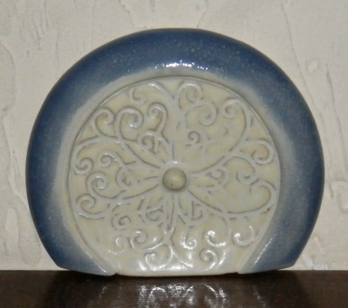 blue and yellow round hobbit door embossed with a swirl pattern