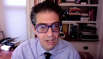 Captura de pantalla de un hombre con gafas hablando frente a una estantería, mirando ligeramente hacia un lado