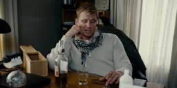 Dolph Lundgren sits down and has a drink.