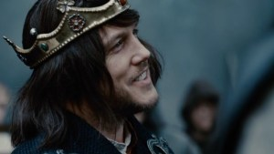 Lochlyn Munro, wearing a wig and plastic crown, portrays the light-hearted King Raven.