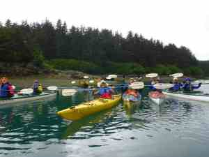Our yoga-kayak fleet at the Hobbit Hole, ready to set off for the 8-mile paddle around Inian Island!
