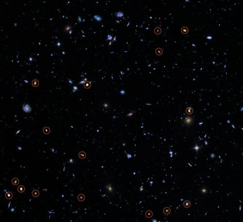 This image combines a background picture taken by the NASA/ESA Hubble Space Telescope (blue/green) with a new very deep ALMA view of this field (orange, marked with circles). All the objects that ALMA sees appear to be massive star-forming galaxies. This image is based on the ALMA survey by J. Dunlop and colleagues, covering the full HUDF area.