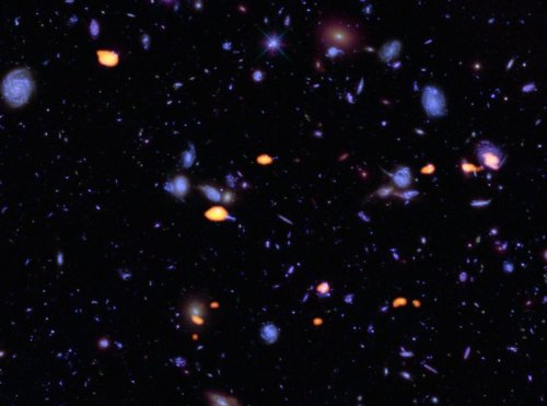 A trove of galaxies, rich in carbon monoxide (indicating star-forming potential) were imaged by ALMA (orange) in the Hubble Ultra Deep Field. The blue features are galaxies imaged by Hubble.This image is based on the very deep ALMA survey by Manuel Aravena, Fabian Walter and colleagues, covering about one sixth of the full HUDF area.