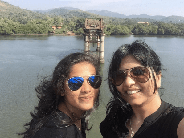 Image of two Girls in goa wearing aviator sunglasses and standing in front of the broken bridge in south Goa