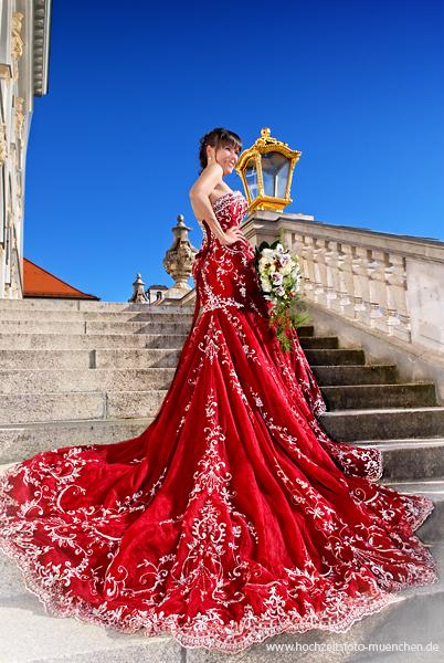 Fotogutschein als Hochzeitsgeschenk: Schöne Braut im rotem Hochzeitskleid im Schloss Nymphenburg