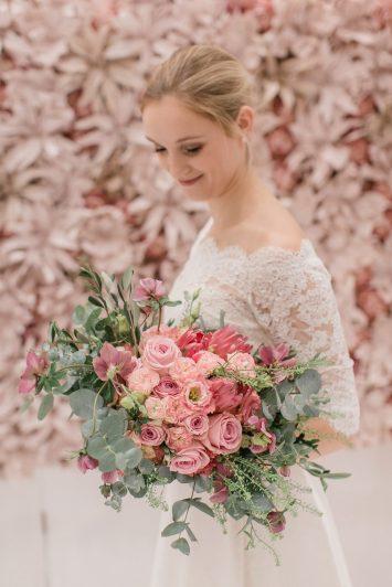 Braut im Hochzeitskleid und rosa Brautstrauß