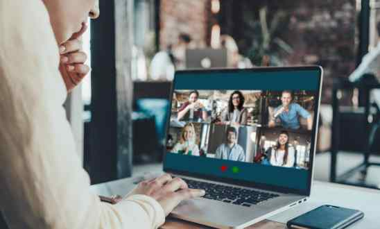 Person leans over laptop with a Zoom meeting with six participants