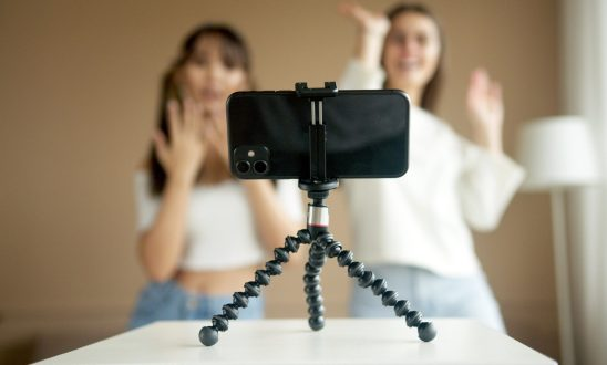 Two influencers dance in front of a cell phone on a tripod