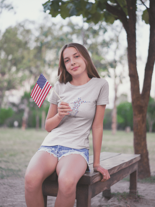 teen girl waving a little american flag wearing a t shirt mockup at the park a20710