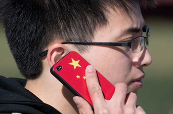 A man talks on a mobile phone featuring a Chinese flag near Tiananmen Square in Beijing on November 13, 2012. China's Communist Party will on November 15 unveil the new set of top leaders who will run the country for the next decade, one day after its week-long congress ends.    AFP PHOTO / Ed Jones        (Photo credit should read Ed Jones/AFP/Getty Images)