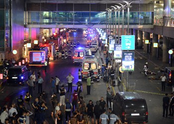 Medics and security members work at the entrance of the Ataturk Airport after explosions in Istanbul, Tuesday, June 28, 2016. Two explosions have rocked Istanbul's Ataturk airport, killing several people and wounding others, Turkey's justice minister and another official said Tuesday. A Turkish official says two attackers have blown themselves up at the airport after police fire at them. The official said the attackers detonated the explosives at the entrance of the international terminal before entering the x-ray security check. (IHA via AP) TURKEY OUT
