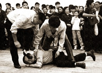 ** File ** Police detain a Falun Gong protester in Tiananmen Square as a crowd watches in Beijing in this Oct. 1, 2000 file photo. China has failed to live up to promises to improve human rights for the 2008 Olympics in Beijing despite death penalty reforms and increased freedoms for foreign reporters, Amnesty International said in a report released Monday April 30, 2007. (AP Photo/Chien-min Chung)