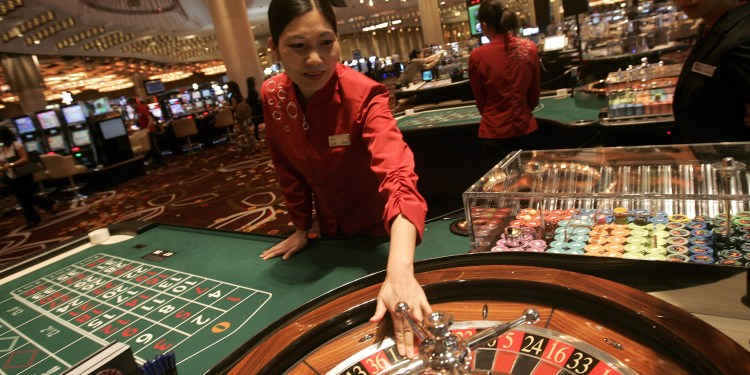 epa01748349 A croupier is pictured on the gaming floor of the 420,000 square foot 'City Of Dreams' casino, in Macau, China, 01 June 2009. The complex features a casino, three hotels and a purpose built theatre. EPA/STR