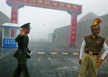 """(FILES) In this photograph taken on July 10, 2008, a Chinese soldier (L) and an Indian soldier stand guard at the Chinese side of the ancient Nathu La border crossing between India and China.  India's foreign minister announced plans on April 25, 2013, to visit China amid a border dispute, saying both countries had a mutual interest in not allowing it to """"destroy"""" long-term progress in ties. According to officials in New Delhi, a platoon of Chinese troops set up a camp inside Indian territory on April 15, 2013. India has since called on the Chinese soldiers to withdraw, but several meetings between local army commanders and diplomats from both sides have failed to resolve the stand-off.  AFP PHOTO/ Diptendu DUTTA/ FILESDIPTENDU DUTTA/AFP/Getty Images"""