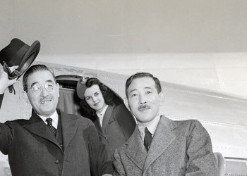 (Original Caption) Waving his hat, Saburo Kurusu, Japan's Special Ambassador, boards a plane at LaGuardia Field, where he paused on his air trip from Tokyo to Washington. With him is Morito Morishima, Consul General in New York, who greeted the envoy. The plane's hostess seems very much interested.