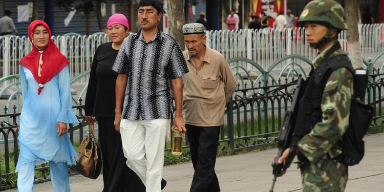 A Chinese paramilitary policeman (R) watches as an ethnic Uighur family passesby outside the Grand Bazaar in the Uighur district of the city of Urumqi in China's Xinjiang region on July 14, 2009. A mosque was closed and many businesses were shuttered a day after police shot dead two Muslim Uighurs, as ethnic tensions simmered in restive Urumqi.   AFP PHOTO / Peter PARKS (Photo credit should read PETER PARKS/AFP/Getty Images)