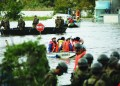 "Fire department workers (C) evacuate residents from a flooded area in Kawagoe, Saitama prefecture on October 13, 2019, one day after Typhoon Hagibis swept through central and eastern Japan. - At least 15 people are dead and nine others missing, officials said on October 13, a day after powerful Typhoon Hagibis slammed into Japan, unleashing ""unprecedented"" rain and catastrophic flooding. (Photo by STR / JIJI PRESS / AFP) / Japan OUT"