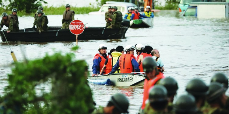 """Fire department workers (C) evacuate residents from a flooded area in Kawagoe, Saitama prefecture on October 13, 2019, one day after Typhoon Hagibis swept through central and eastern Japan. - At least 15 people are dead and nine others missing, officials said on October 13, a day after powerful Typhoon Hagibis slammed into Japan, unleashing """"unprecedented"""" rain and catastrophic flooding. (Photo by STR / JIJI PRESS / AFP) / Japan OUT"""