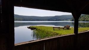 A mountain lake viewed through a window in a wooden bridge