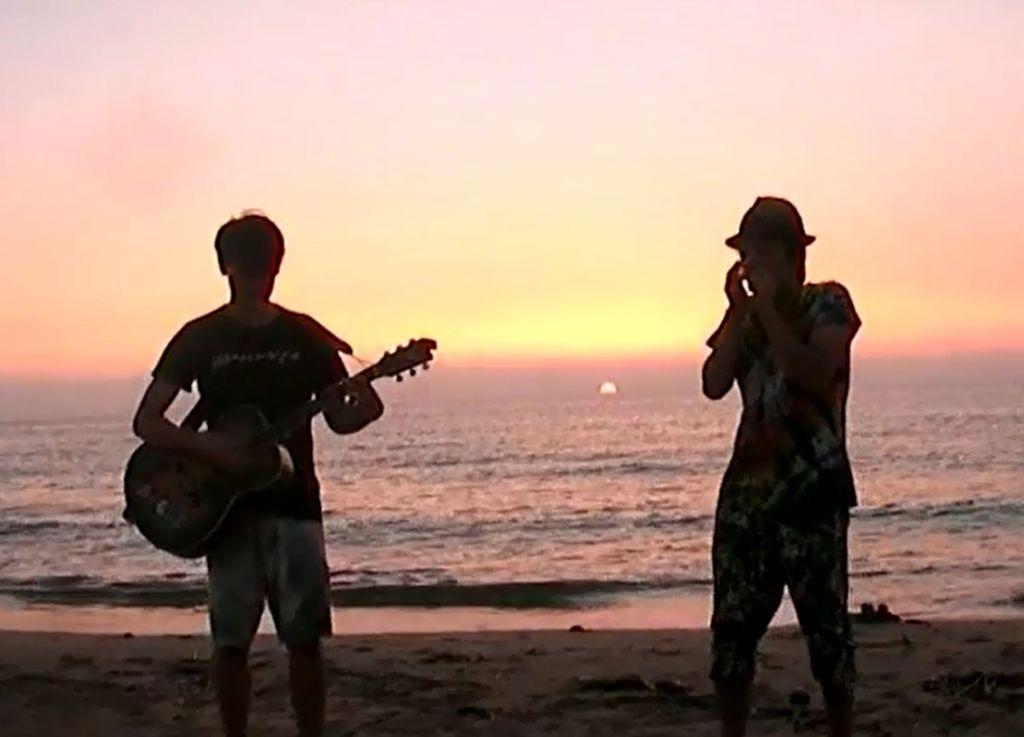 夕日の浜辺でセッションする渓と行人