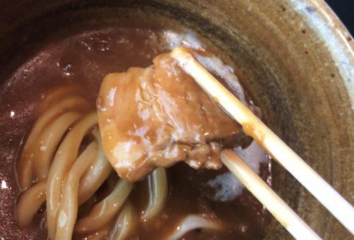 カレーうどんの角煮を箸で持った