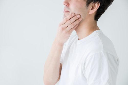 白いTシャツを着た顎を触る男性