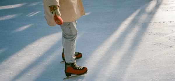 faceless fit woman skating on ice rink in daylight