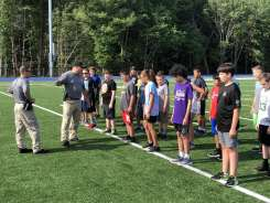 Students stand in formation during orientation with Officer Casey Surprenant (left) and Detective Dan Ford (right) on the first day of the Holbrook Junior Police Academy. (Courtesy Photo)