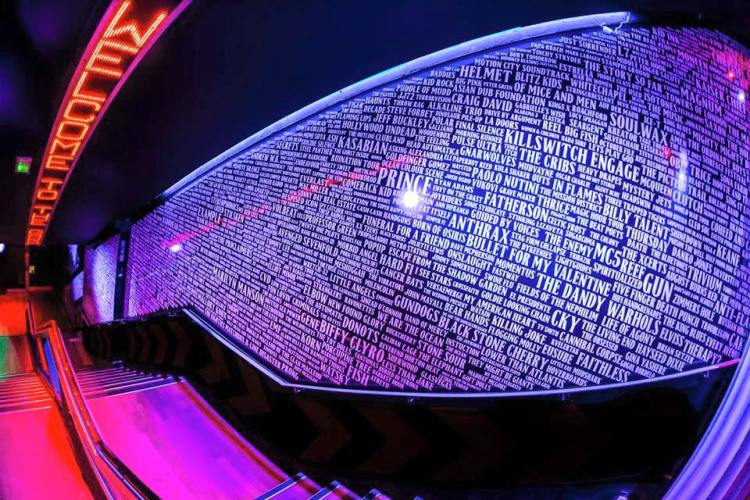 staircase at the entrance of the garage nightclub glasgow with the names of every band and artist that have played at the venue written on the wall