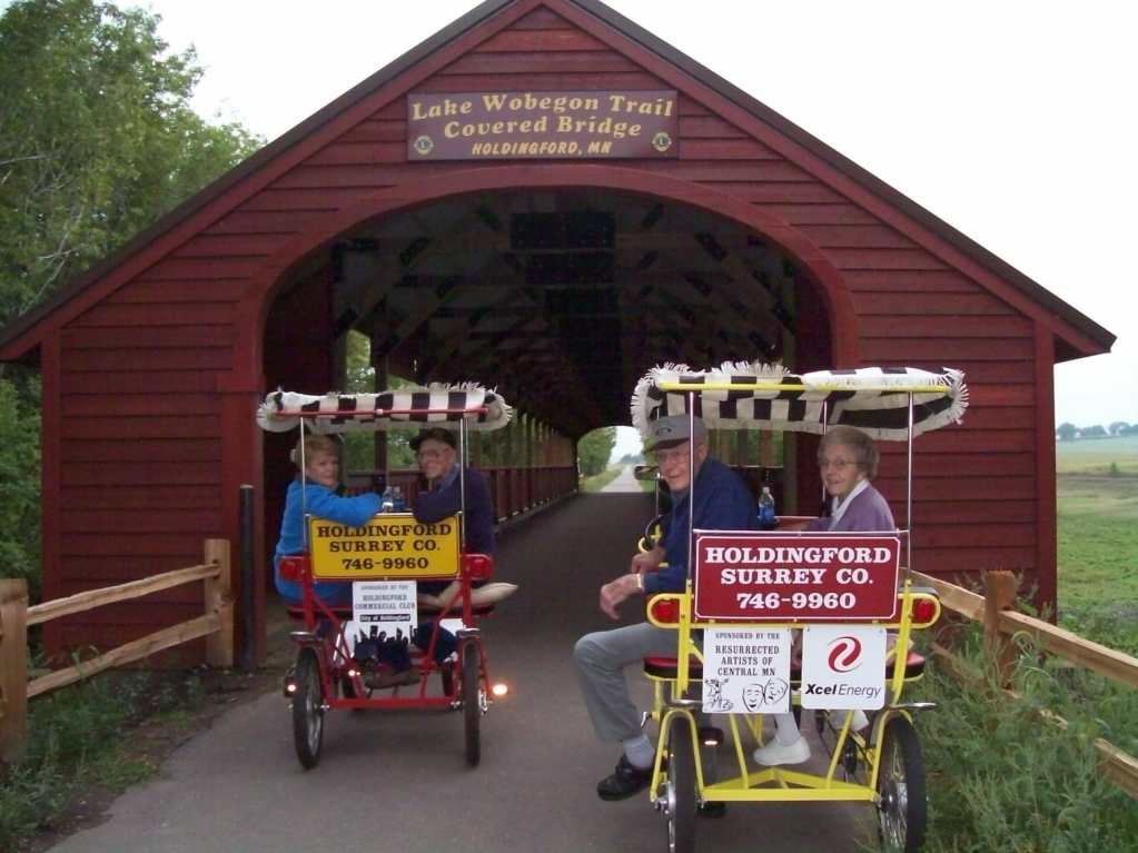 Two couples riding surries under the Lake Wobegon Trail Covered Bridge in Holdingford.
