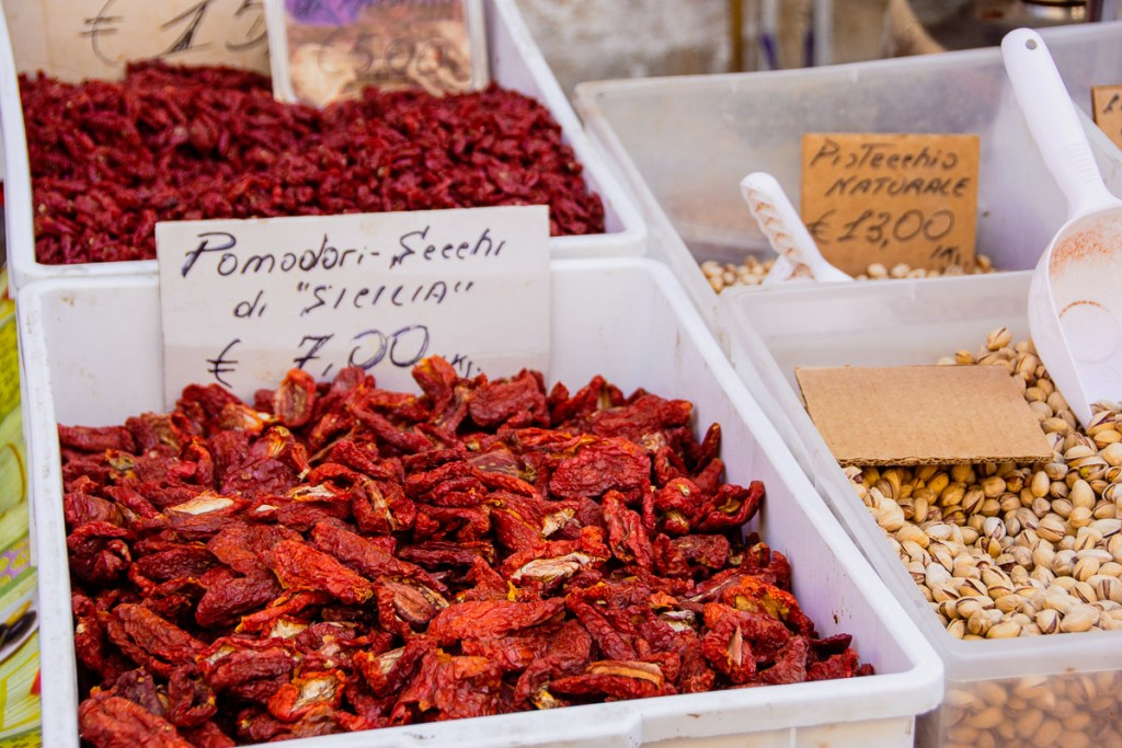 Sun dried tomatoes and pistachios for sale at the Ortigia market