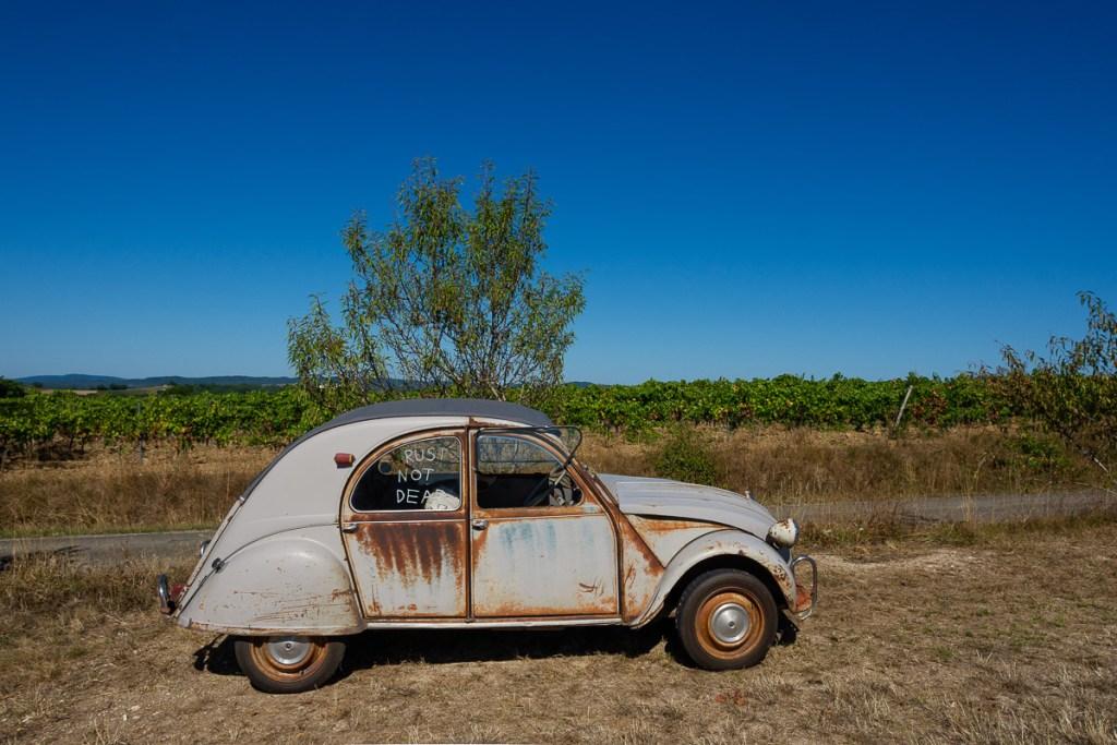 a rusty old Citroen outside a vineyard, France