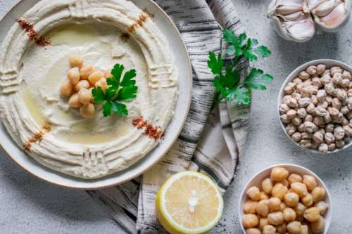 chickpea hummus served garnished with cumin powder, chill, olive oil and parsley