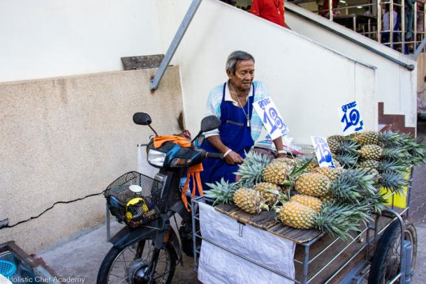 pineapple farmer selling his pineapples at the local market in Phuket