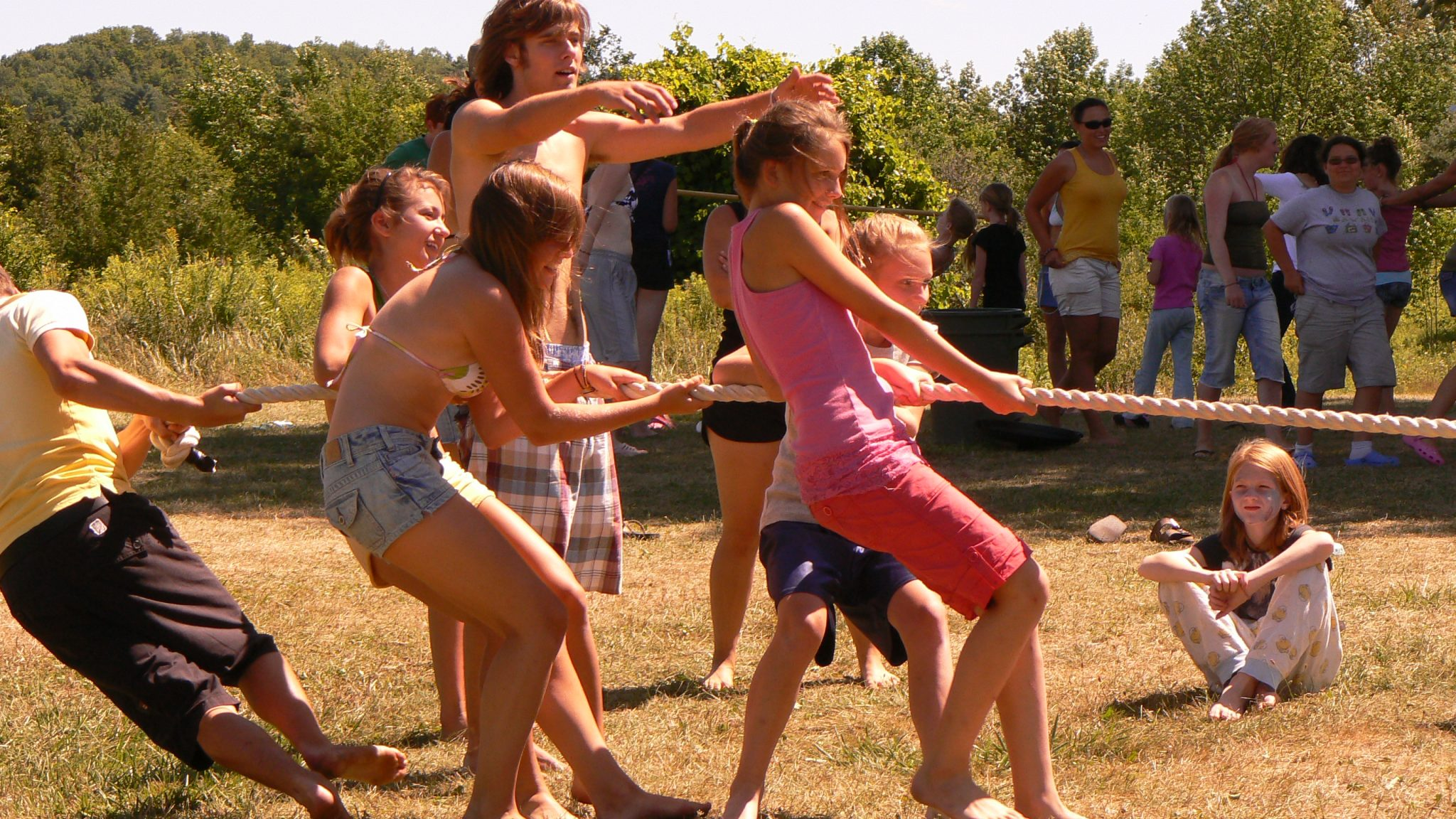 Group of campers playing tug of war being encouraged by their counselor